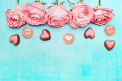 Light pink roses border with chocolate heart and love Message Sign on turquoise background, top view. Festive greeting card royalty free stock photo