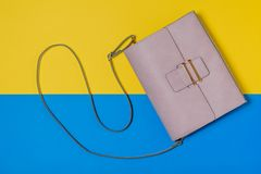 Light pink women`s bag on yellow and blue background. Modern women`s leather accessory. The view from the top. Flat lay stock photo