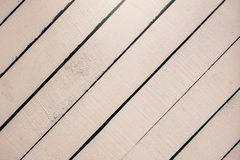 Light pink wooden surface, texture close-up. Rustic natural diagonal planks with cracks, scratches for modern design stock images