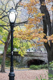 Light pole in Central Park in the fall with bridge Royalty Free Stock Images
