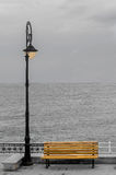 Light pole with colored bench on seafront, seaside, cloudy day, dawn Royalty Free Stock Image