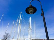 Light pole with sail boat masts in background. Black light pole with white sail boat masts in background in harbor, central Maine and blue sky royalty free stock photography