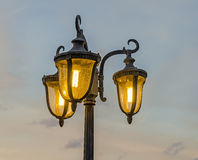 Light pole with three bulbs, orange light, blue sky, close up, outdoor. Stock Images