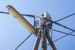 Light pole wires. Light pole and various wiring cables against blue sky royalty free stock photo