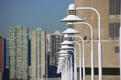 Light poles over city skyline Royalty Free Stock Images