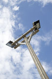 Light poles in the park. Spotlights post on blue sky Stock Images