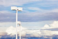 Light Posts and Cloudy Sky. White parking lot light post add an abstract minimalist look against a cloudy sky.  Copyspace available in this image Stock Images