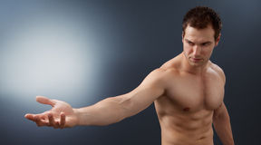 Light and power concept - creative muscular man. Holding bright sphere Stock Photography