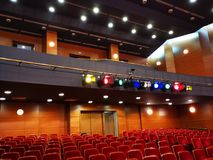 Light projectors with colored filters - theater hall. Light projectors with colored filters in a theater hall and ceiling lights control stock images