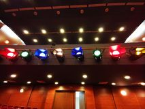 Light projectors with colored filters. In a theater hall and ceiling lights control royalty free stock photo