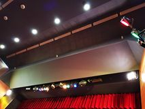 Light projectors with colored filters. In a theater hall and lights control on the ceiling stock photography