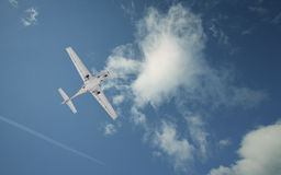 Light propeller airplane on a cloudy sky Royalty Free Stock Photography