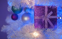 Light purple gift box in white Christmas tree with white light, blue light, teal ornament, purple ornament, white ornament royalty free stock photography