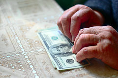 Light purse. Senior woman with hundred dollar bill, selective focus, toned image. Royalty Free Stock Photo