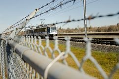 Light rail in the city. Over sharp barbed wire spiral and part of a fence Stock Image