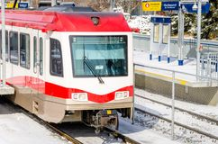 Light Rail Train Pulling out of a Snowy Station. On a Sunny Winter Day Royalty Free Stock Images