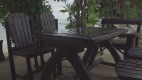 Light rain falls on a lonely table and chairs in outdoor cafe near the beach. Light rain pours on a lone wooden table and chairs in a street cafe amidst tropical stock video