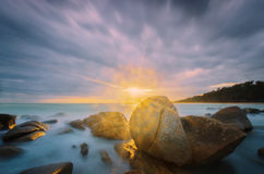 Light ray and bokeh beautiful in seascape. Light ray and rock beautiful in sunset seascape surrounding on the beach Stock Photo