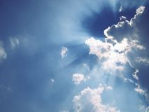 Light ray from sun behind cloud in the blue sky Stock Photos