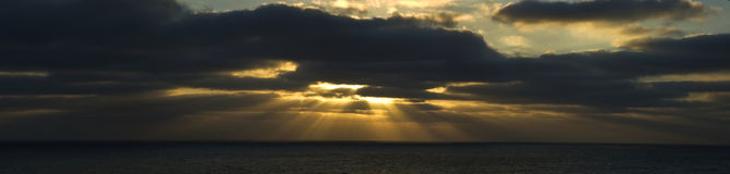 Light Rays Through Clouds. Rays of light shine through clouds over the ocean Stock Photo
