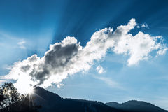 Light rays through clouds over mountain top. At blue sky Royalty Free Stock Images