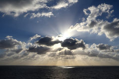 Light rays shine through the group of clouds. In the middle of the sea Stock Photo