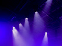 The light rays from the spotlight through the smoke. Lighting equipment on the ceiling. Royalty Free Stock Photography