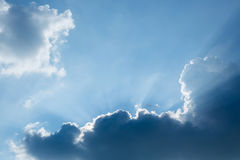 Light rays of sun beam through clouds in clear blue sky Royalty Free Stock Images