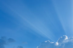 Light rays of sun beam through clouds in clear blue sky Stock Image