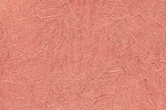 Light red wavy background from a textile material. Fabric with fold texture closeup. Stock Images