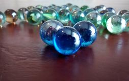 Light reflecting on glass marbles on wooden table Stock Image