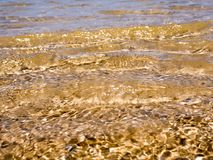 Light reflection on the surface of movement sea. On sand beach Stock Images