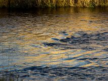 Light reflections on moving water. Yellow light reflections on blue flowing river water create a pattern royalty free stock images