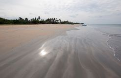 Light reflections in swirling serpentine sand patterns on Nilaveli Beach in Trincomalee Sri Lanka Stock Images