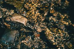 Light reflections in the water of a river. With some rocks under water royalty free stock image