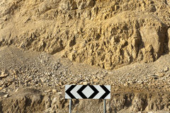 Road Arrows in the Desert. Light-reflective road arrows on the background of a barren desert mountain Stock Images