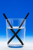 Light refraction. A straw in a glass of water shows light refraction. Blue background Royalty Free Stock Image