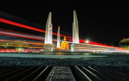 The Democracy Monument is a public monument in the centre of Bangkok, capital of Thailand. The light on the road at night and the city and democracy Monument in royalty free stock image