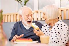 Jolly senior man receiving eclair stock image