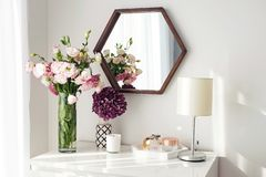 Light room with mirrow, flowers, night lamp and other objects. Modern interior details. Light room with mirrow, flowers, night lamp and other objects stock photo