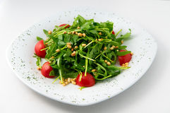 The light salad of arugula and cherry tomatoes with nuts on the white bacground Stock Images