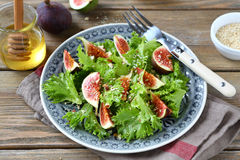 Light salad with figs, lettuce and honey in a plate on napkin Stock Image