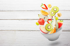 Light salad with flying fresh fruits Royalty Free Stock Photography