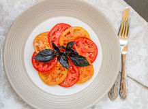Light salad of juicy red and yellow tomatoes and red Basil. Salt and pepper. Gourmet appetizer. Selective focus Stock Image