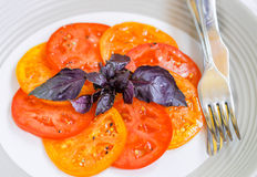 Light salad of juicy red and yellow tomatoes and red Basil. Salt and pepper. Gourmet appetizer. Selective focus Stock Photo