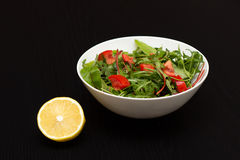 Light salad with tomatoes in white china bowl and lemon stock photo