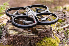 Light scout drone. A small spy quad copter drone over a tree stump ready to take off royalty free stock image