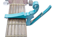 Light sea green string capo with guitar on white background Royalty Free Stock Photos