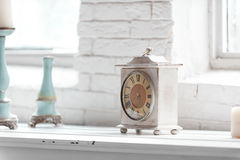 Light shabby chic  interior fragment with clock and candlesticks. On white brick wall background Royalty Free Stock Image