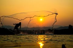 Light and shadow fishermen. Sunset Light and shadow fishermen Royalty Free Stock Image